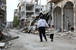 Father and son walk through the ruins of their home town, Homs, Syria. UNHCR / B. Diab