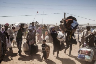 Syrian refugees cross over into the outskirts of Kobani, Turkey after fleeing their home. UNHCR / I. Prickett