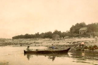 August Jack Khahtsalano, his wife Swanamia (Marrian) and a child in a dugout canoe, looking east at Kitsilano Indian Reserve in 1907. City of Vancouver Archives AM1376-: CVA 1376-203