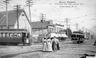 Waiting for transit on (well, near) Broadway has a long history. Photograph shows people waiting for a streetcar on Westminster Avenue (Main Street) between 8th and 9th Avenues. Vancouver City Archives; AM54-S4-: Dist P144