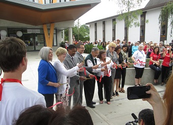 A number of dignitaries were on hand for the ribbon-cutting. The Welcome House is on the left, First CRC on the right.