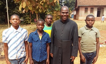 Father Placid with four boys on the only street in Luhombero.