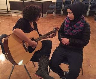 Shadia and a young refugee participating in an art night at Vancouver First CRC.